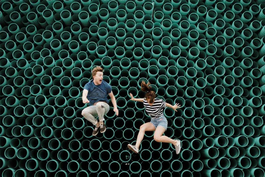 Man and woman lying down on top of pipes