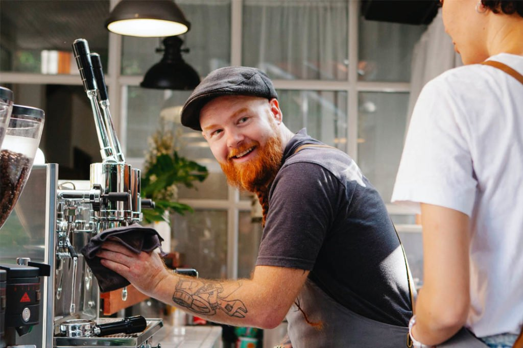 Barista smiling while cleaning the coffee machine