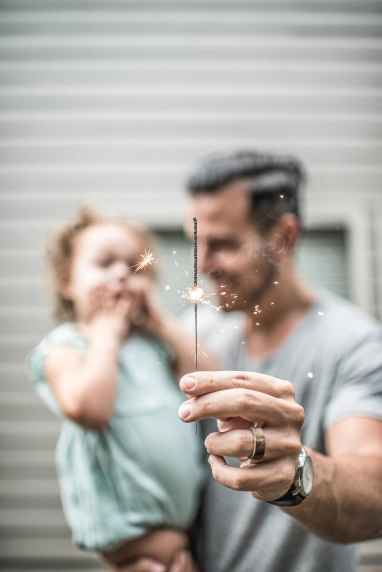 Man carrying his daughter while holding a candlestick firecracker